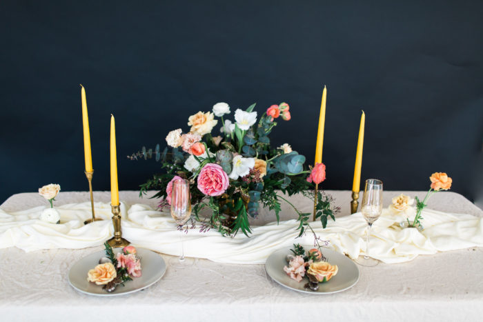 floral bouquet on a table with candles and place settings