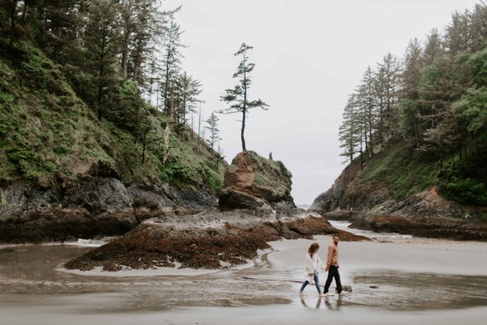 two people walking on the sand at dead man's cove in washington